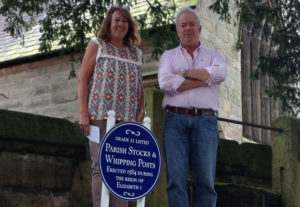 Church Inn owner Tim with Angela from the Mobberley Parish Council photographed next to the famous Mobberley Stocks and whipping posts opposite the Church Inn who helped with the sign funding